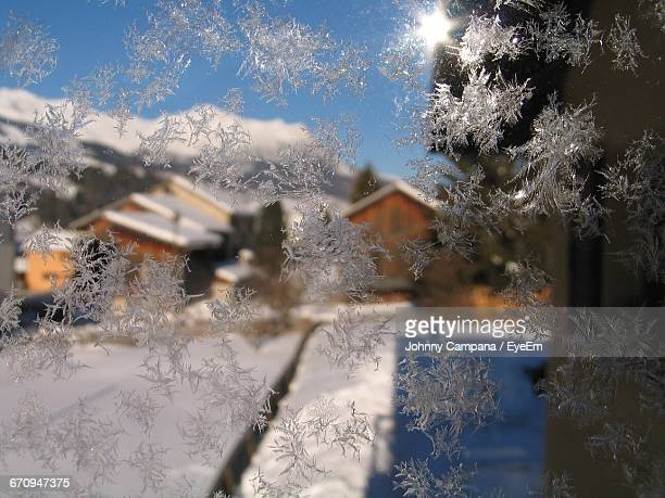 Close-Up Of Snow On Glass Against Houses