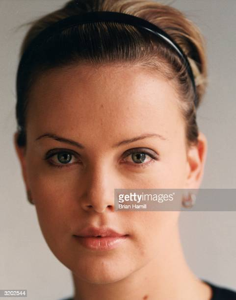 Closeup of South Africanborn actor Charlize Theron wearing a headband in her hair and a gold earrings New York City RESTRICTED PLEASE INQUIRE