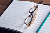Close-up of spectacles and pencil on organizer at table