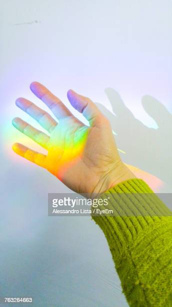 Close-Up Of Spectrum On Hand Against Wall