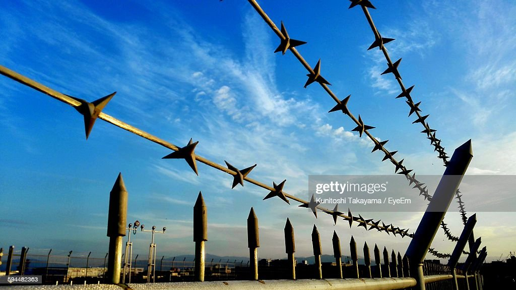 Close-Up Of Spiked Metallic Fence Against Blue Sky