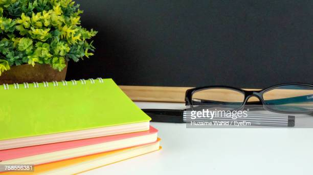 Close-Up Of Spiral Notebooks And Eyeglasses On Table