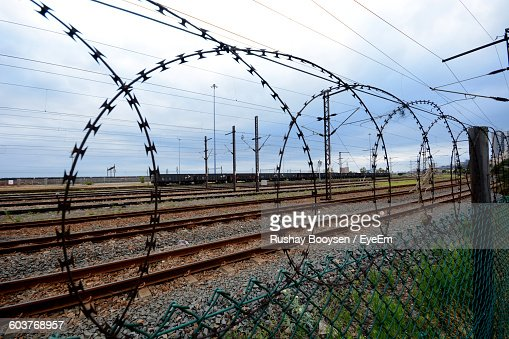 Close-Up Of Spiral Razor Wire On Chainlink Fence By Railroad Track