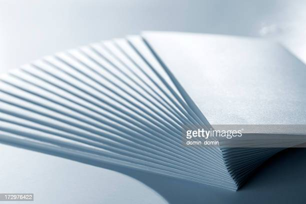 Close-up of stack of paper envelopes, blue toned