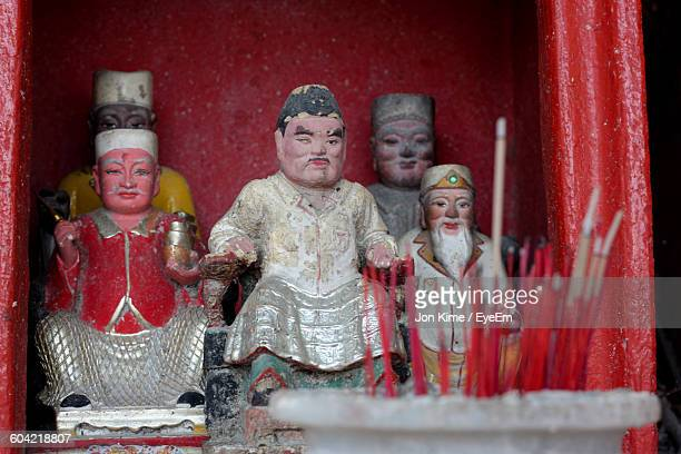 Close-Up Of Statues And Incense Stick In Temple