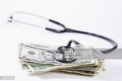 Close-up of stethoscope on US dollar bills