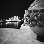 Close-Up Of Stone Bollard Against Illuminated Hungarian Parliament Building By Danube River