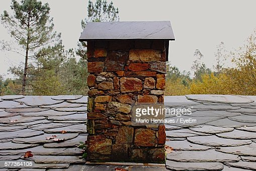 Close-Up Of Stone Chimney On House Roof