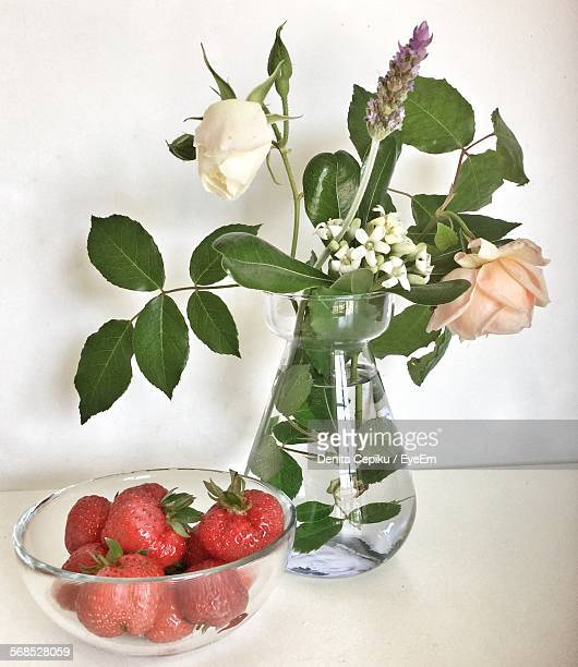 Close-Up Of Strawberries In Bowl With White Flowers Vase On Table