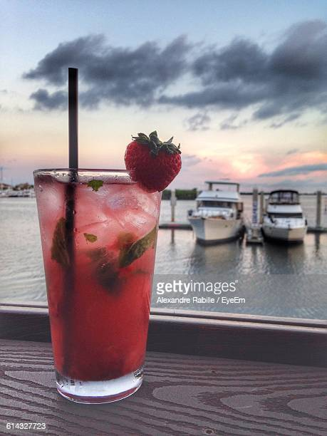 Close-Up Of Strawberry Mojito On Table Against Boats At Port