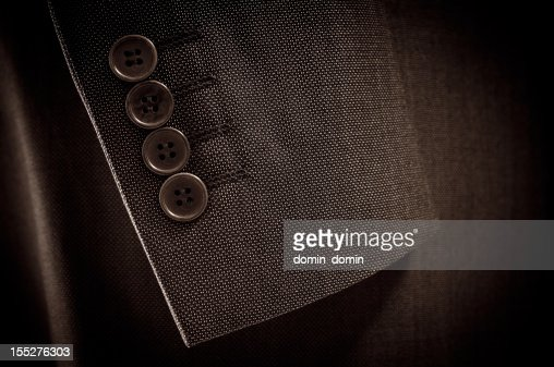 Close-up of suit's sleeve and buttons in brown colour
