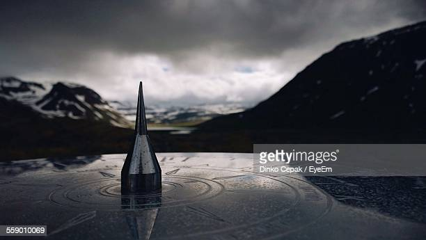 Close-Up Of Sundial With Mountains On Background