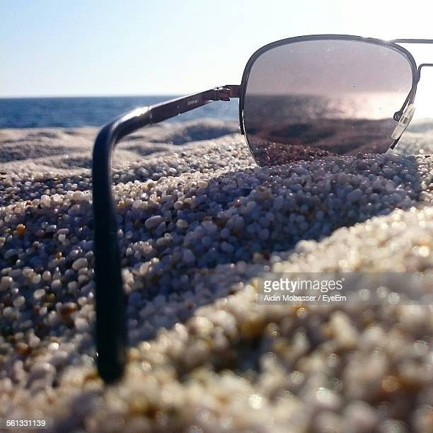 Close-Up Of Sunglass On Gravel In Beach