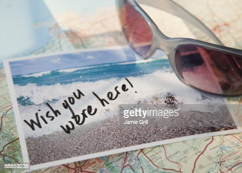 Close-up of sunglasses and postcard on map
