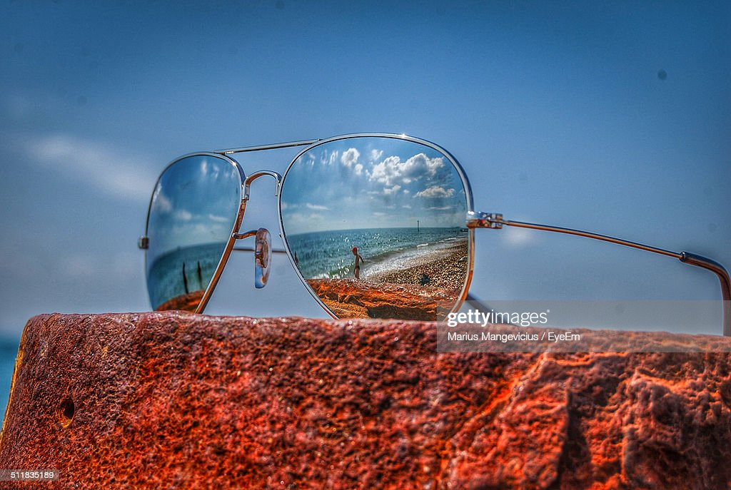 Close-up of sunglasses on rock with beach reflections