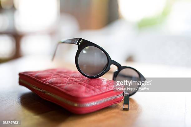 Close-Up Of Sunglasses With Purse On Table At Home