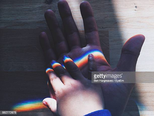 Close-Up Of Sunlight Falling On Child And Father Hands On Table