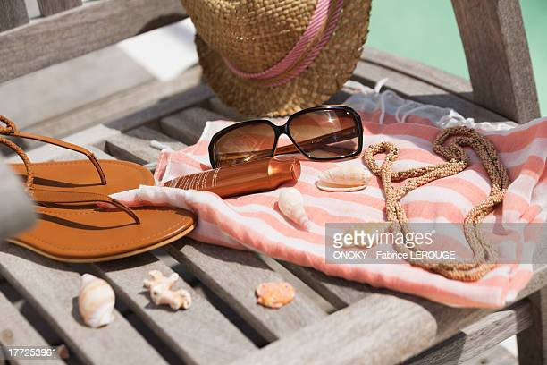 Close-up of suntan lotion and sunglasses on beach chair with sun hat and flip-flops