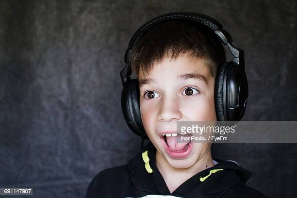 Close-Up Of Surprised Boy Listening Music Against Wall