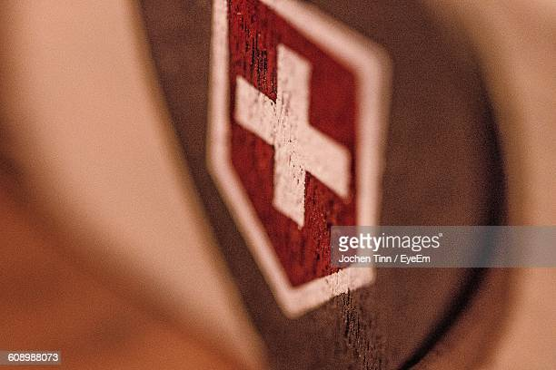 Close-Up Of Swiss Flag On Wood