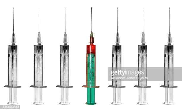 Close-up of syringes over white background