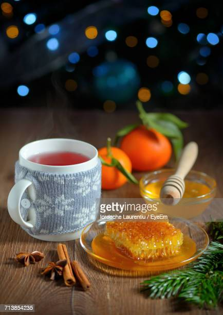 Close-Up Of Tea By Honey And Spices On Table Against Illuminated Christmas Lights
