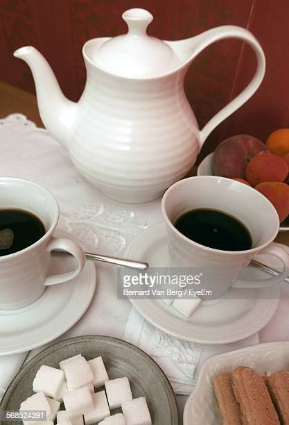Close-Up Of Tea In Cups Served With Bread Slices On Table