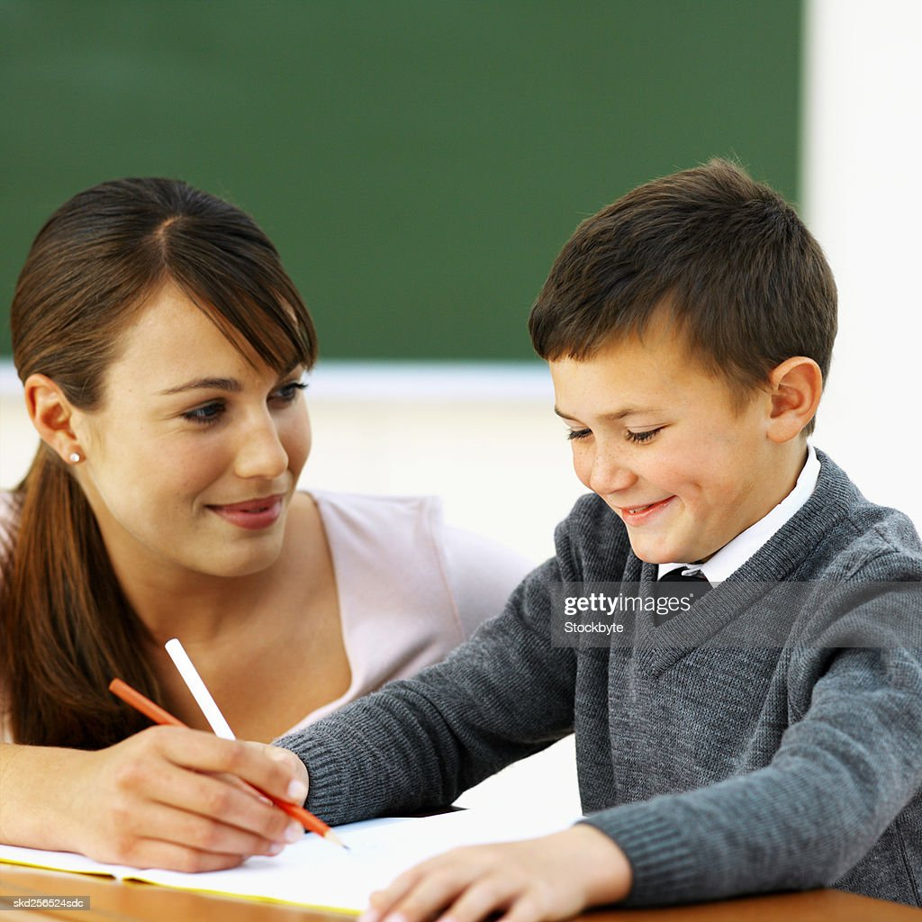 Close-up of teacher assisting student with lesson (10-11) : Stock Photo