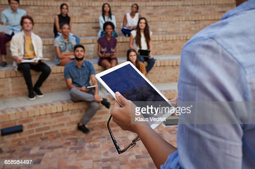 Close-up of teacher holding tablet in auditorium : Stock Photo