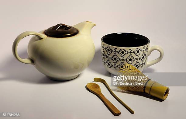 Close-Up Of Teapot With Cup And Wooden Spoon On White Background