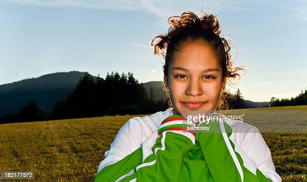 Close-up of teenage girl in sports vest in a field at sunset