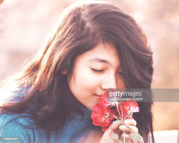 Close-Up Of Teenage Girl Smelling Red Roses At Park