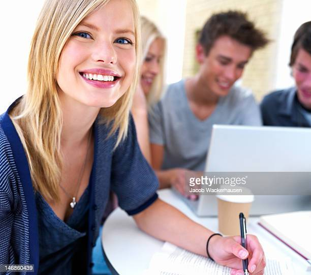Close-up of teenage girl smiling with friends in the background