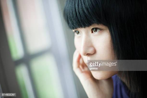 のクローズアップを吸うティーンエイジャーの女の子に座ってウィンドウ、悲しみます。