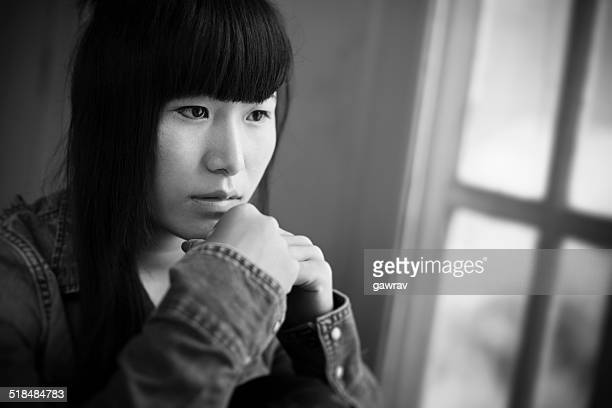 Close-up of teenager girl sitting near window with sadness.