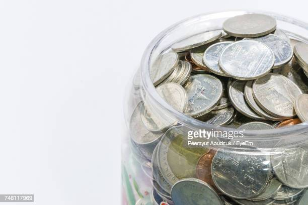 Close-Up Of Thai Coins In Container Against White Background