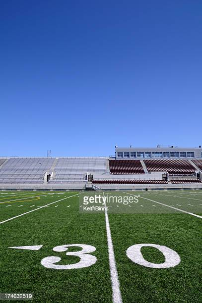 A close-up of the 30 yard line on a football field