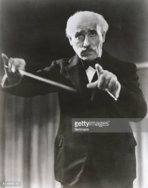A closeup of the celebrate Italian composer Arturo Toscanini as he conducts an orchestra at an unindentified venue