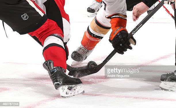 A closeup of the game puck between two sticks on a faceoff between the Ottawa Senators and the Anaheim Ducks at Canadian Tire Centre on December 19...