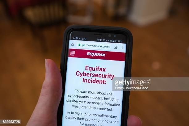 Closeup of the hand of a man holding a mobile phone open to the web site of credit bureau Equifax with text on the website reading 'Equifax...