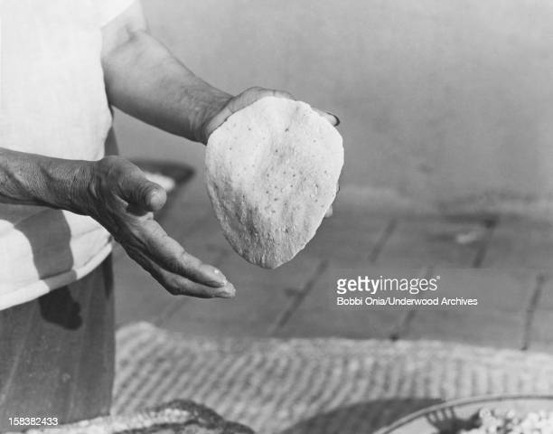 Closeup of the hands of a Native American woman as she makes cornflour tortillas California late 1920s or early 1930s