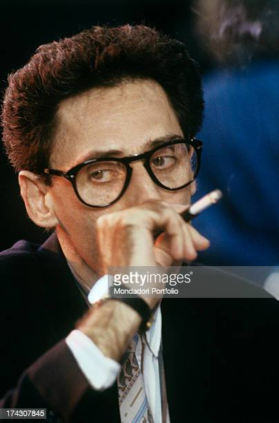 Closeup of the Italian songwriter and singer Francesco Battiato known as Franco Battiato while he is smoking a cigarette Battiato is staring downward...