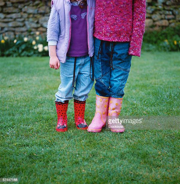 close-up of the legs of two girls (6-8) standing in rain boots on a lawn