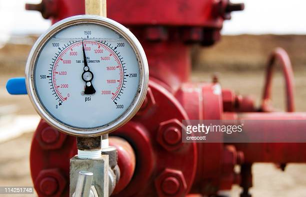 Close-up of the meter of a red wellhead pressure gauge