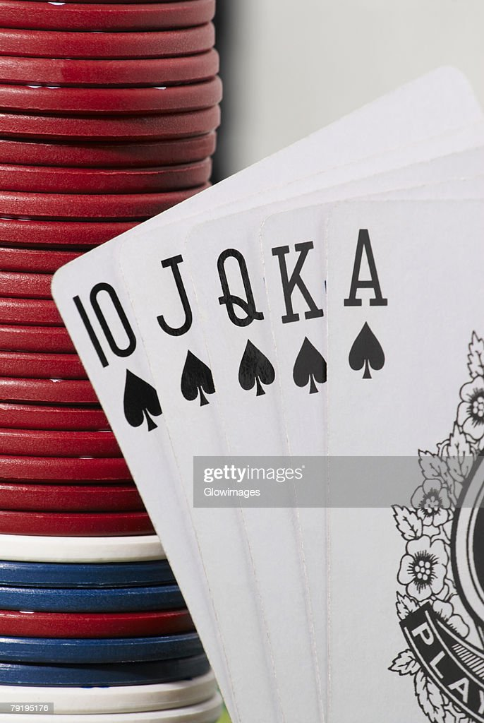 Close-up of the poker of spades with a stack of gambling chips