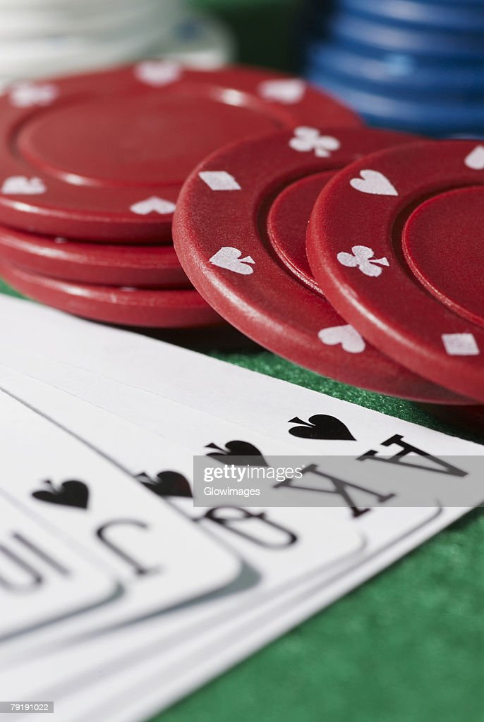 Close-up of the poker of spades with gambling chips on a gambling table