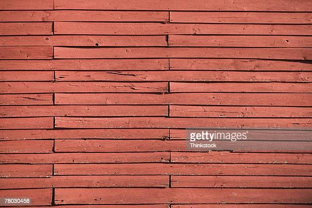 Close-up of the red wooden texture on the side o f a barn.