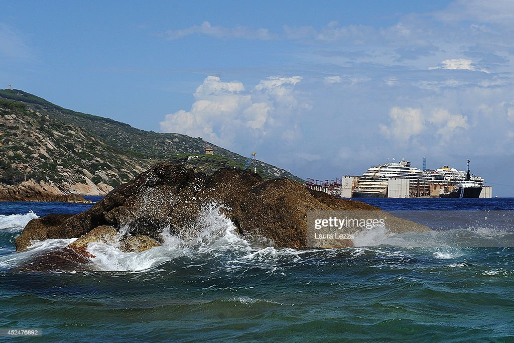 A close-up of the rock which caused the cruise ship Costa Concordia to sink, as the shipwrecked remains are re-floated in the distance on July 21, 2014 in Isola del Giglio, Italy. Technicians are working to finish the refloat of the ship and aim to start towing the ship to the port of Genoa for dismantling on Wednesday, July 23.