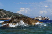 A closeup of the rock which caused the cruise ship Costa Concordia to sink as the shipwrecked remains are refloated in the distance on July 21 2014...