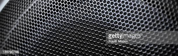 Closeup of the round circles on a black speaker grill.